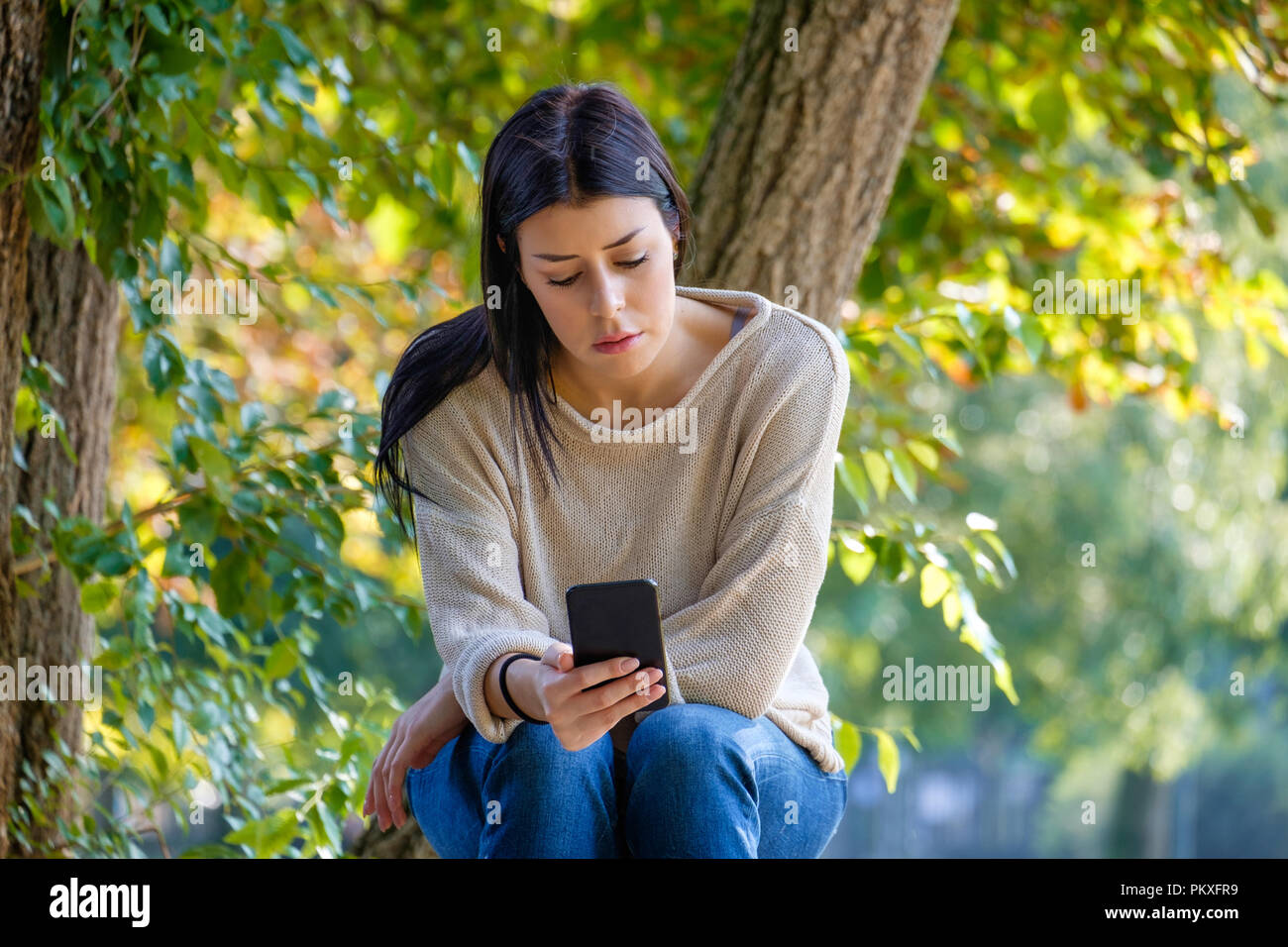 Sad girl watching her smartphone and feeling alone waiting social notifications - Stock Image