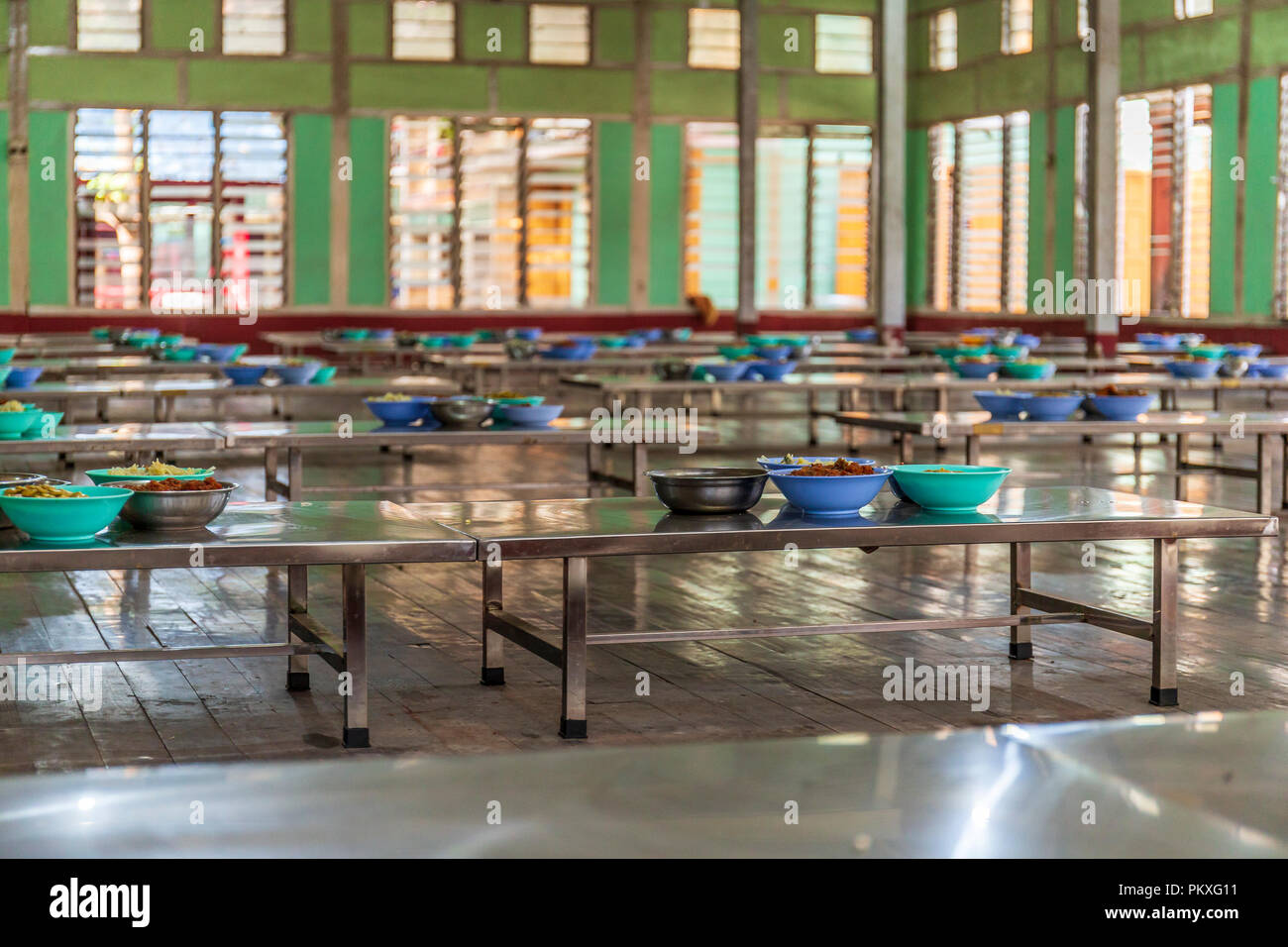 Decked tables waiting for monks at Mahagandayon monastery, Myanmar. - Stock Image