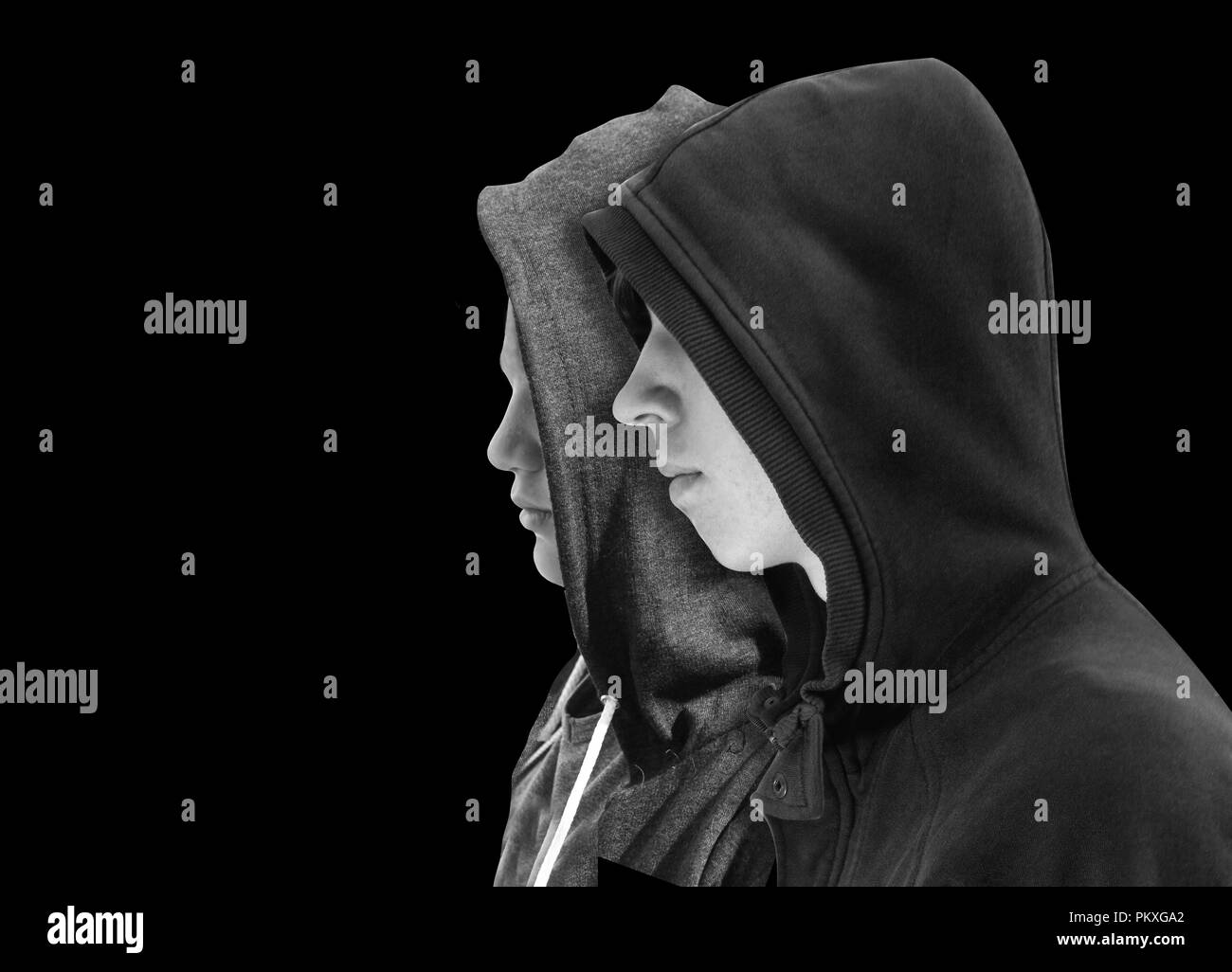 Two troubled teenage boys with black hoodie standing next to each other in profile isolated on black background. Black and white image. - Stock Image