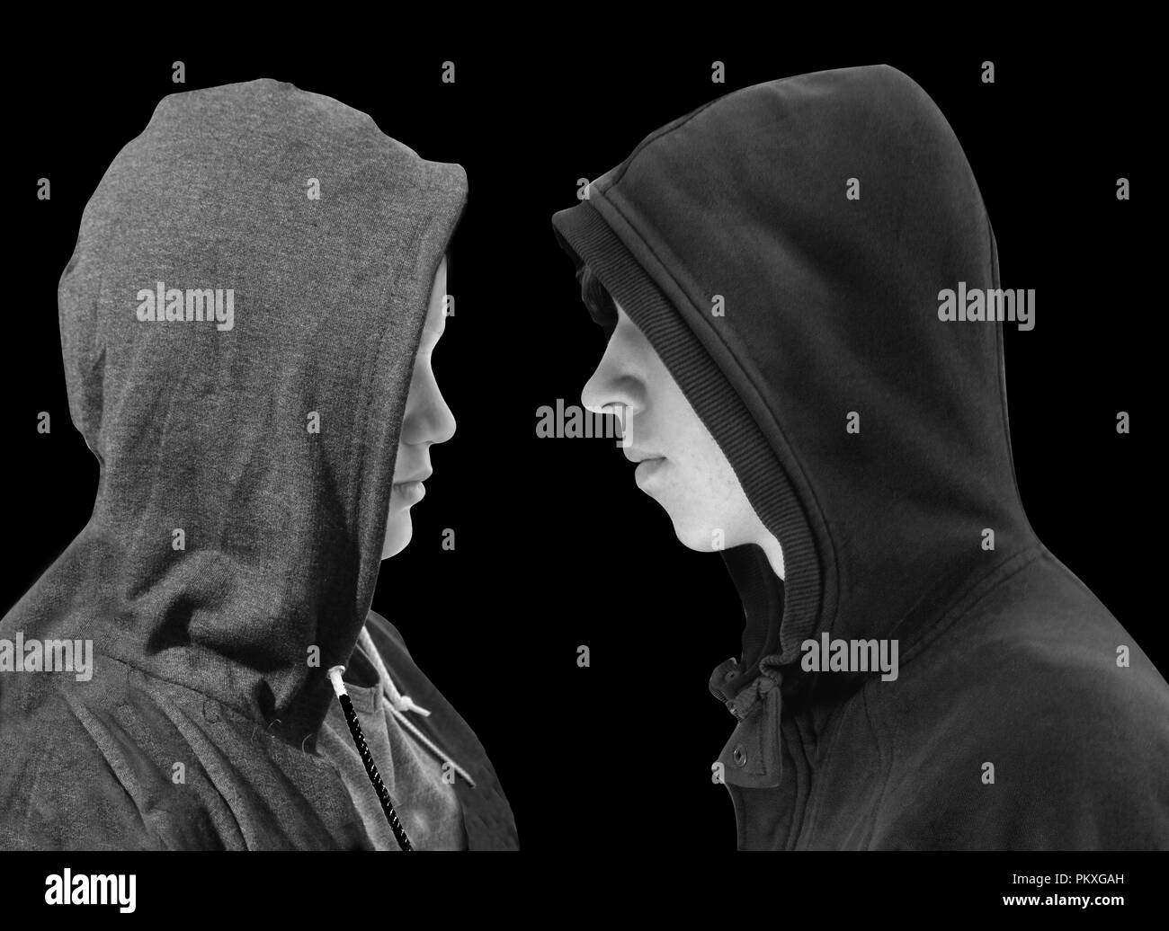 Two troubled teenage boys with black hoodie standing in front of each other in profile isolated on black background. Black and white image. - Stock Image