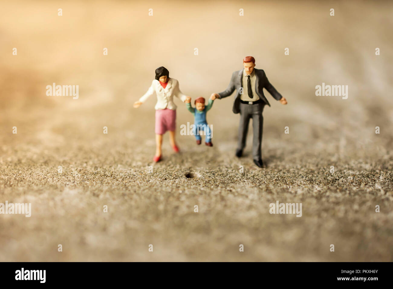 Happy Family Concept. Miniature Figure of Father, Mother and Son Walking Outdoor to Making Activities together - Stock Image