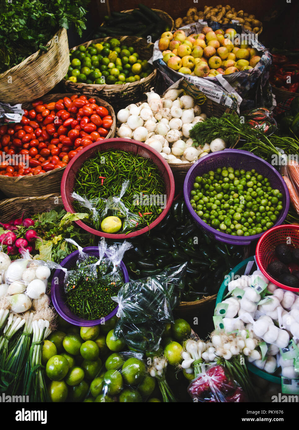 Autumn harvest of fresh organic vegetables on sale at a market stall - colorful bowls of tomato, beans, chillies, garlic, mushrooms, limes and apples Stock Photo