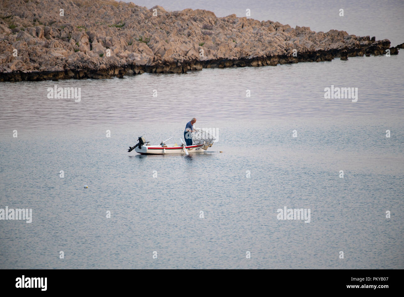 Old traditional fisherman in Croatia on a small wooden boat catching fish with fishing cage, pod Stock Photo