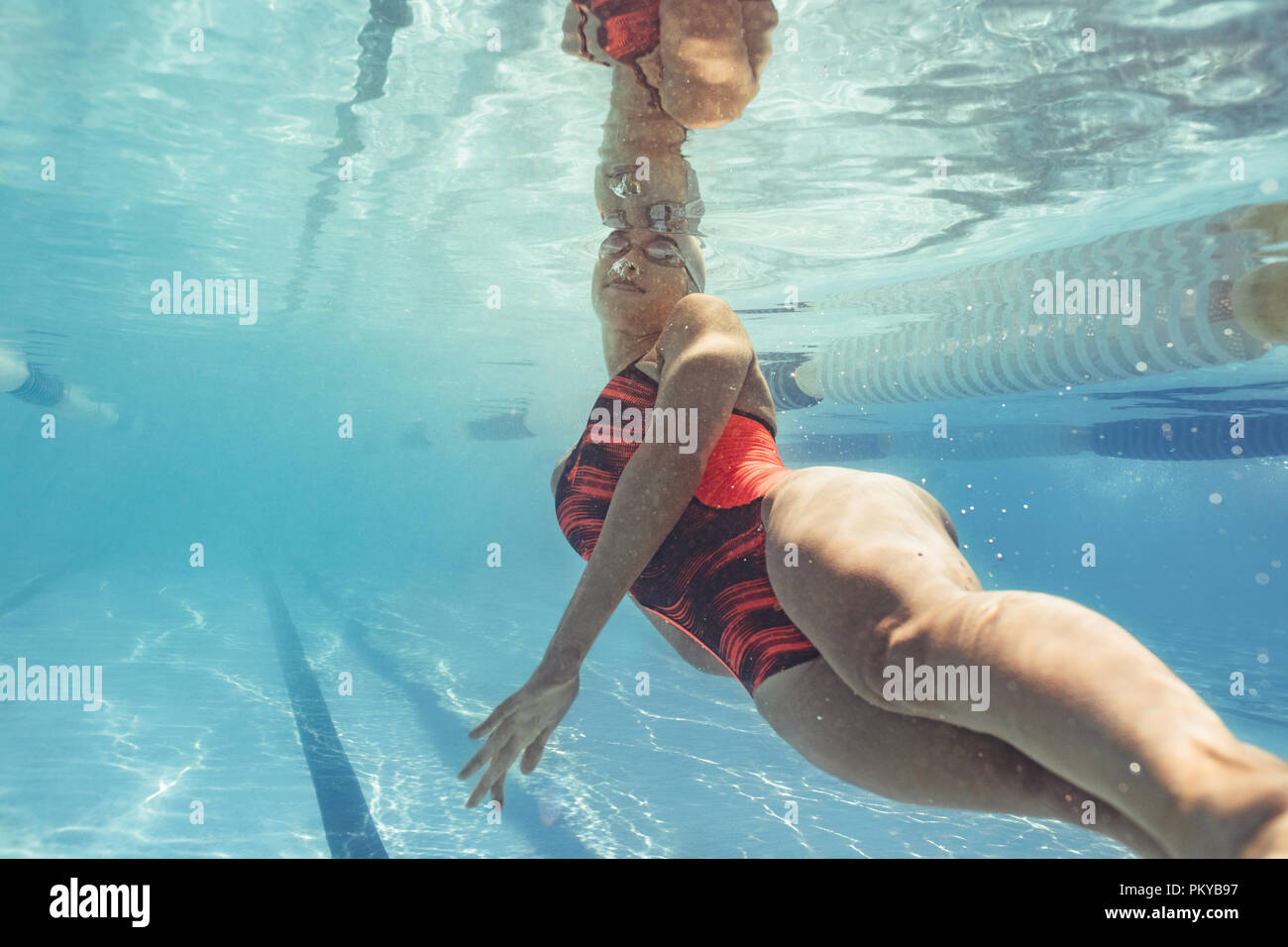 Underwater shot of female swimmer in action inside pool. Fit young female swimmer training in the pool. Stock Photo
