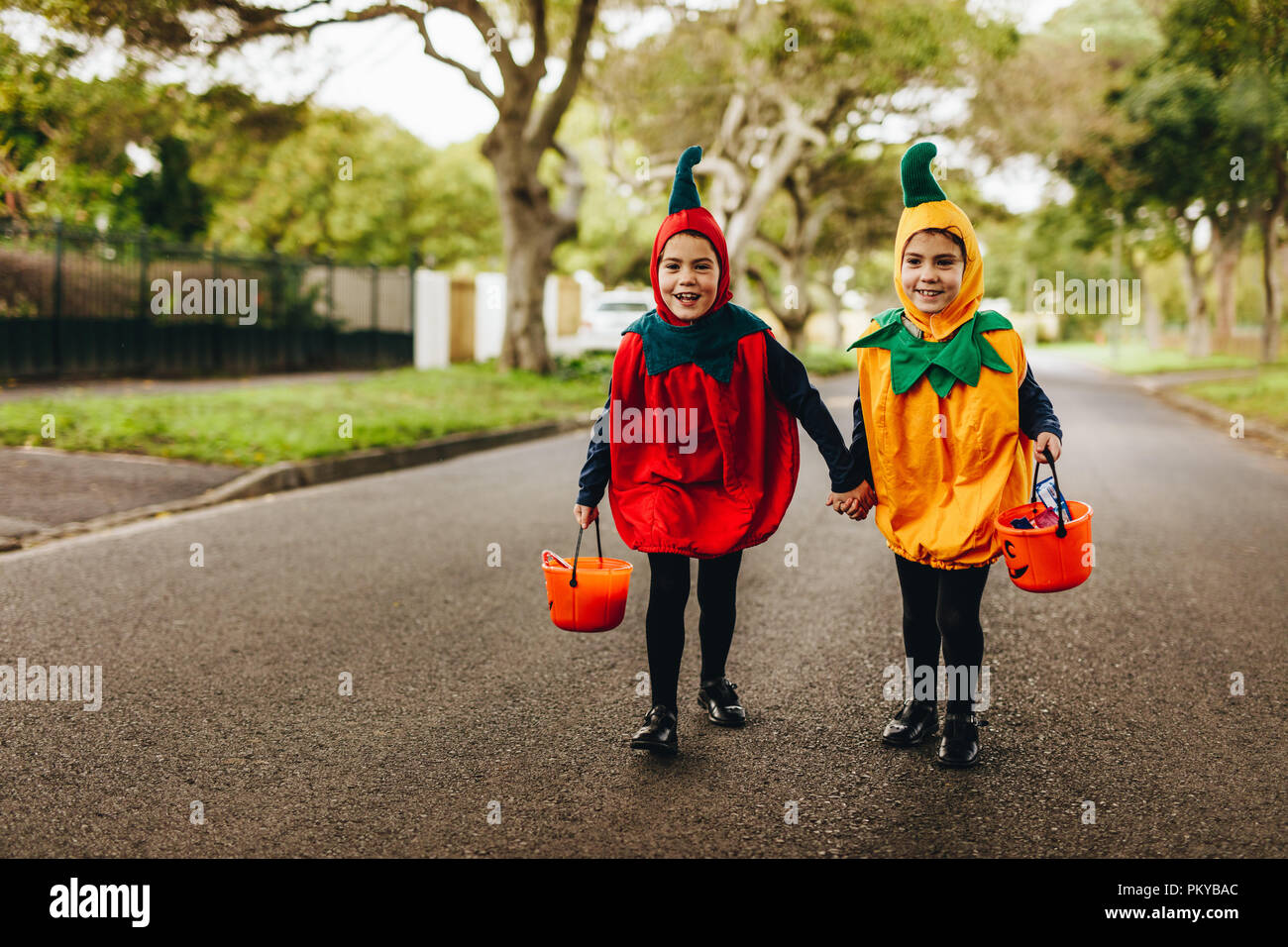 two little girls in halloween costume trick or treating on the road