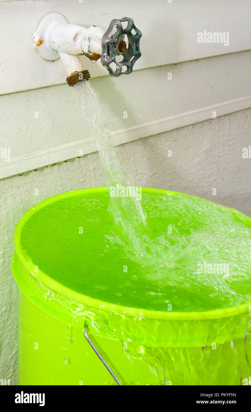 Water rushing out of outdoor spigot into green pail. - Stock Image