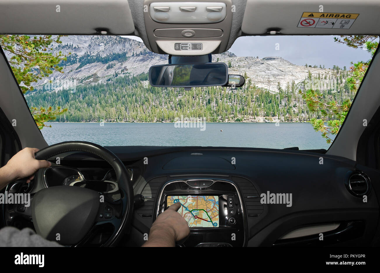 Driving a car while using the touch screen of a GPS navigation system towards a beautiful green valley and lake in Yosemite National Park, California, - Stock Image