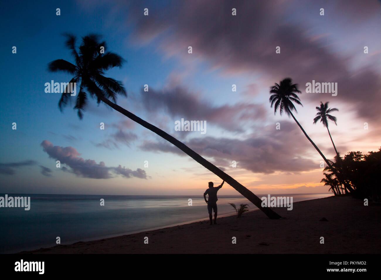 Sunset silhouettes near Lepa Beach, Upolu Island, Samoa. - Stock Image