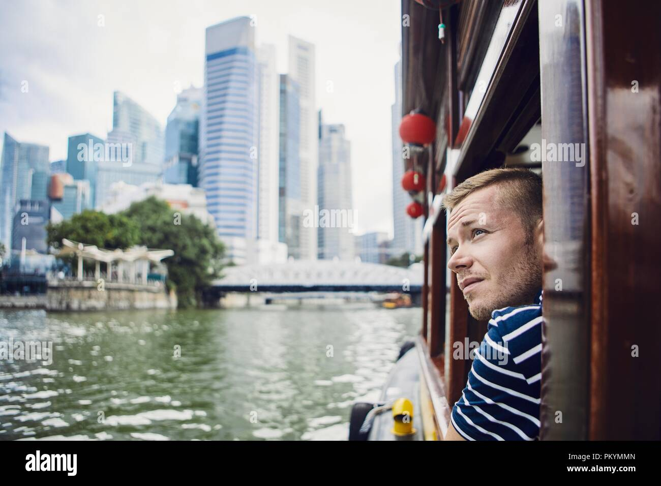 Young man exploring city and looking out from river boat in Singapore. - Stock Image