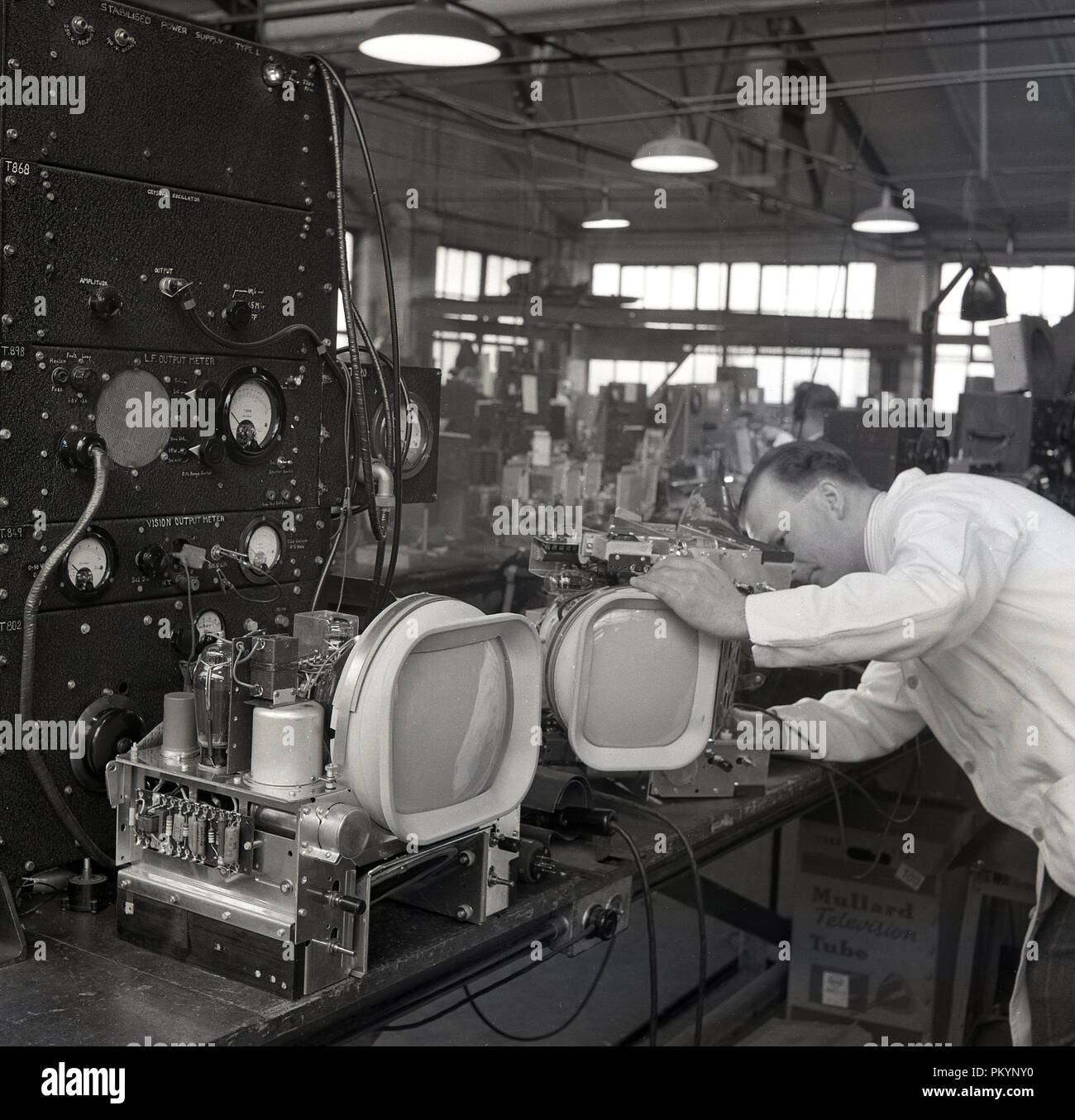 1950s, historical, white-coated male technician working on the components of television sets at the factory of Bush Radio, a leading british consumer electronics company in this era. - Stock Image