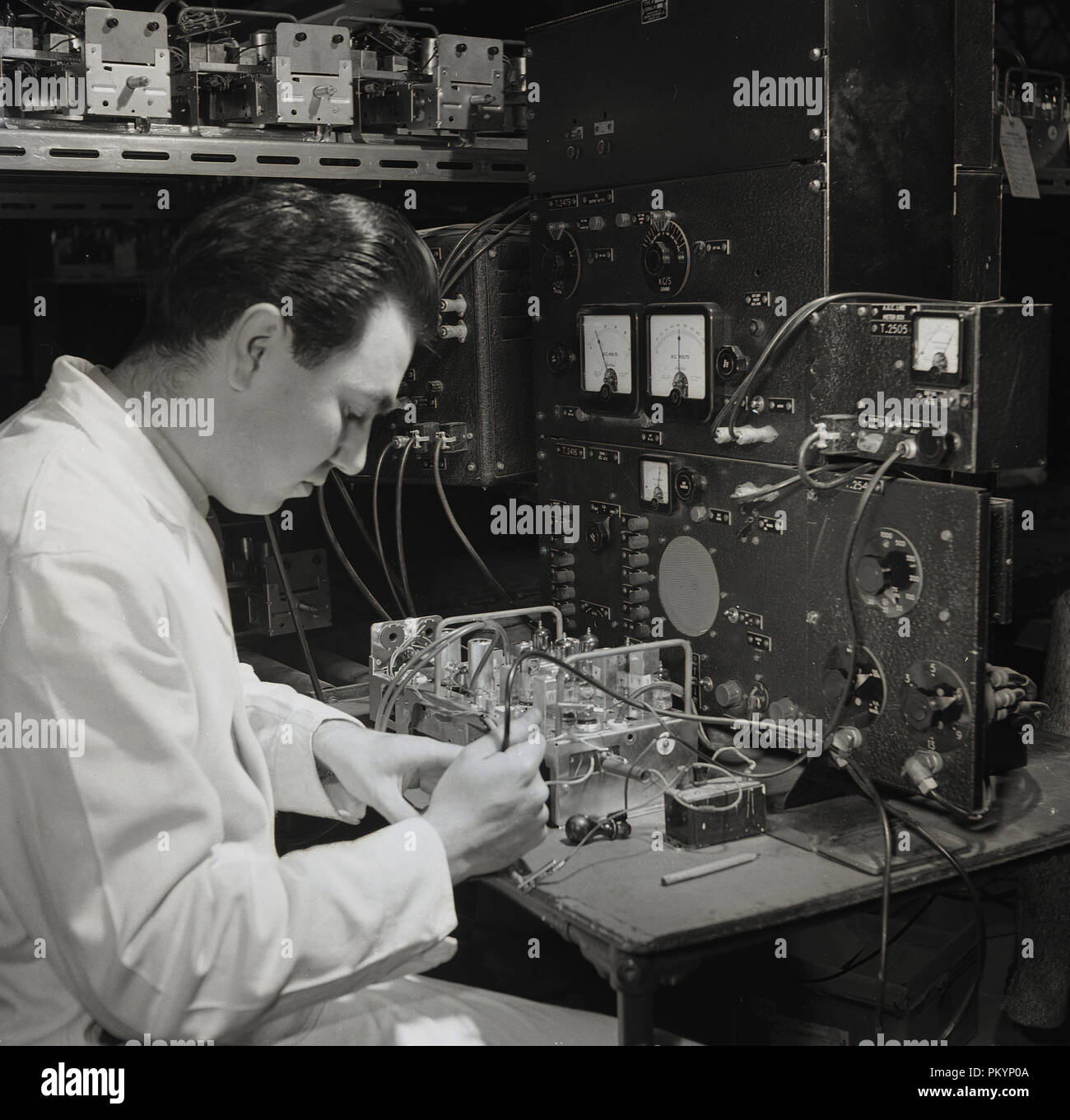 1950s, historical, white-coated male technican testing the internal components of a radio receiver at Bush Radio, a leading British consumer electronics company in this era. - Stock Image