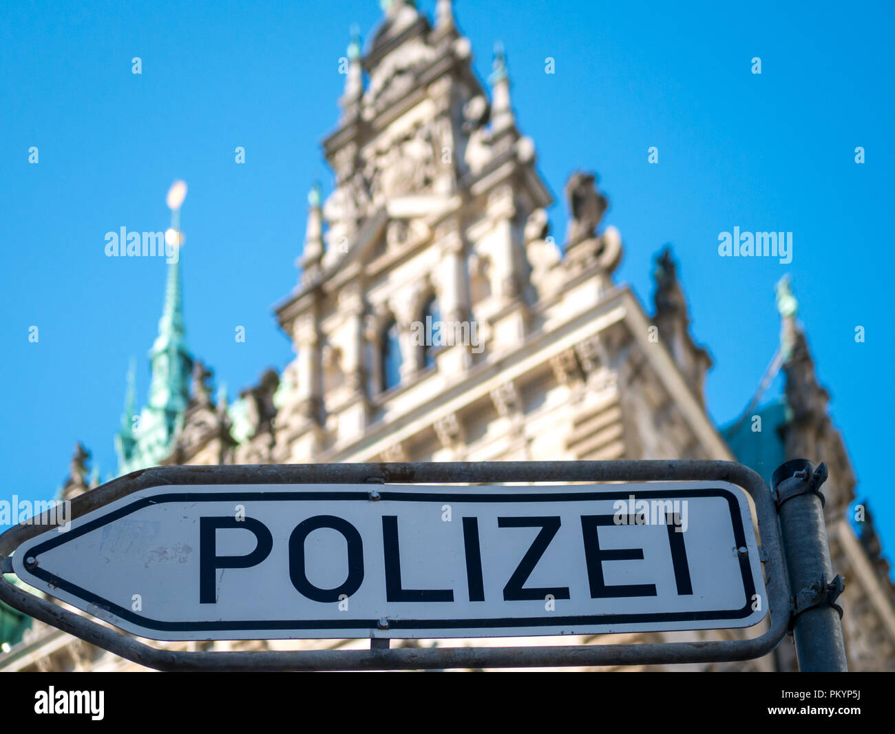 Polizei Hinweis Schild vor verschwommenem Hintergrund der Türme des Hinterhofs des Rathauses Hamburg bei blauem Himmel bei Tageslicht. - Stock Image
