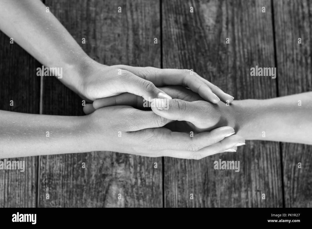 male and female hands holding each other against a wooden background. - Stock Image