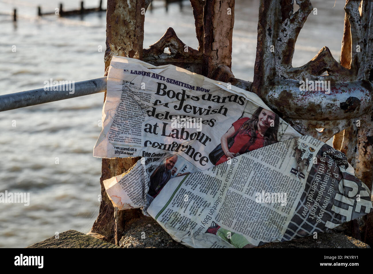 Windswept tabloid featuring an article about the Labour Party anti-antisemitism row stuck to the rusty side of an old jetty in Bognor Regis Stock Photo