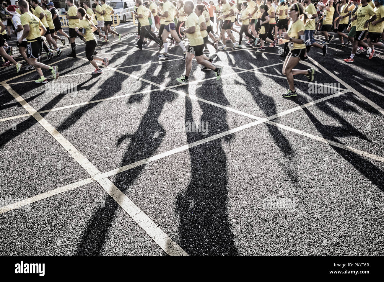Long shadows cast by runners at city fun run event. - Stock Image