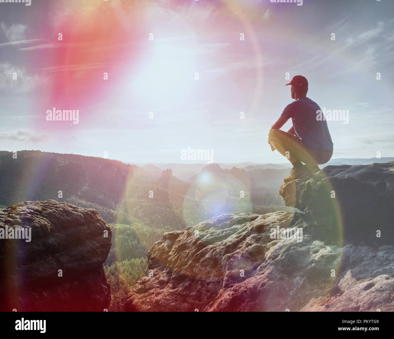 Hiker watching to Sun at horizon. Beautiful moment the miracle of nature. Colorful mist in valley. Man hike. - Stock Image