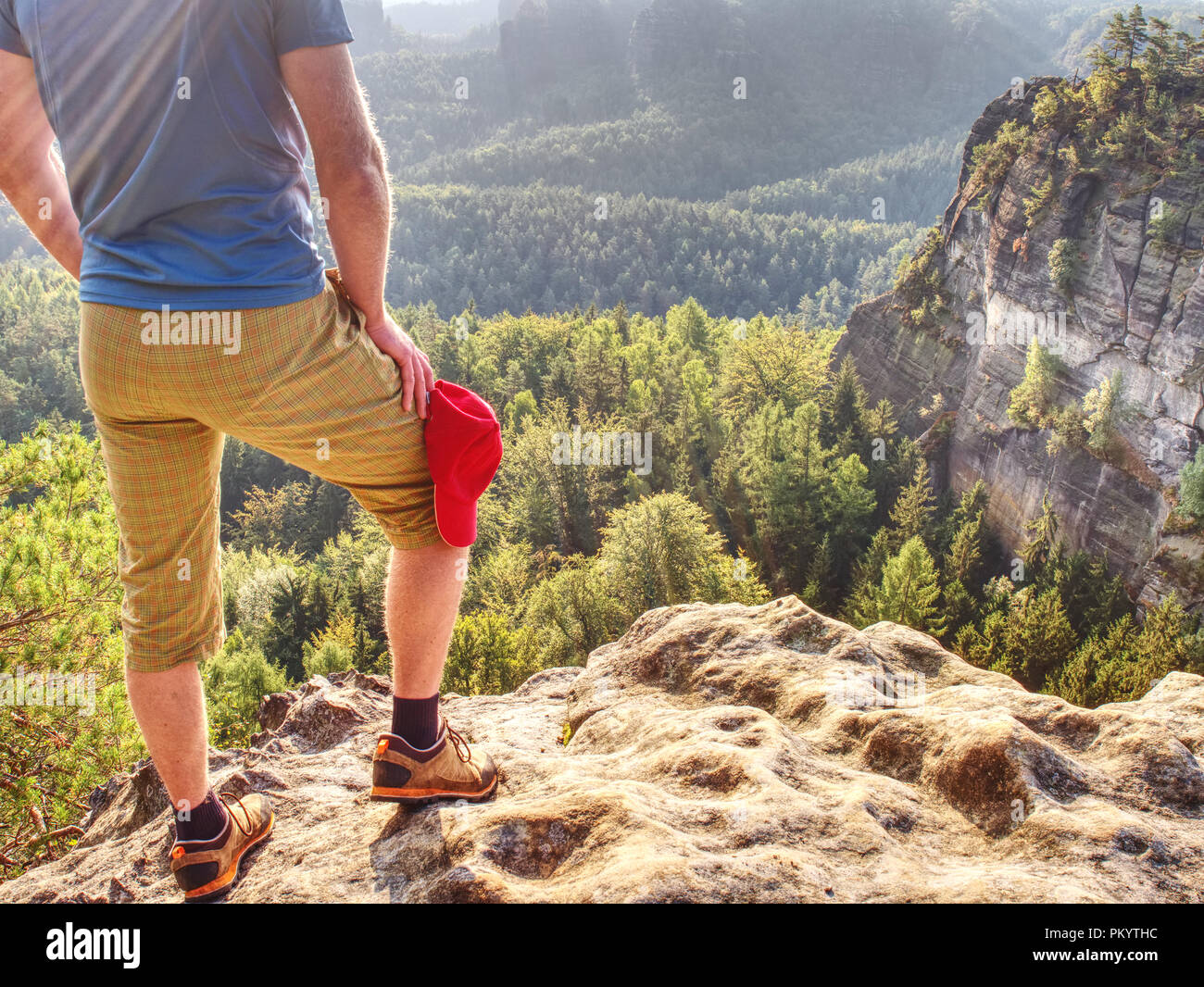 Hiker stays on a rocky ridge and enjoy view over long valley to horizon Stock Photo