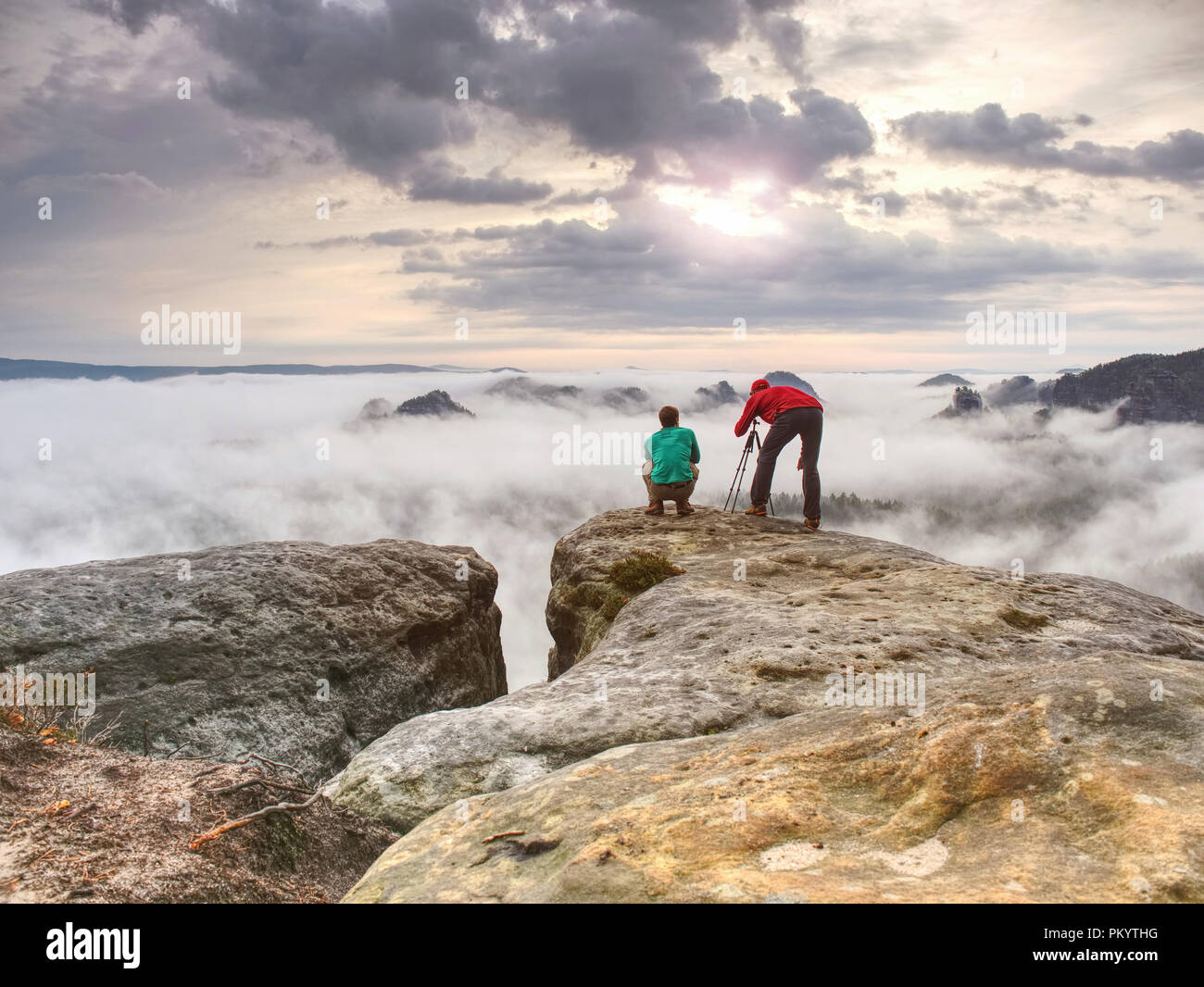 Travel photographer man taking nature video of mountain lookout. Hiker tourist professional photographer and videographer on adventure vacation shooti - Stock Image