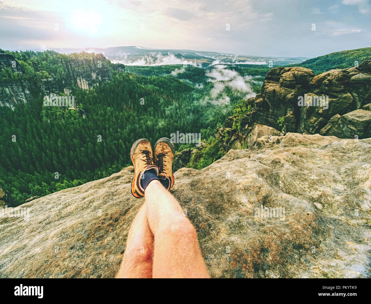 Hiker man take a rest on mountain peak. Male legs on sharp summit and hiker enjoy spectacular view. - Stock Image
