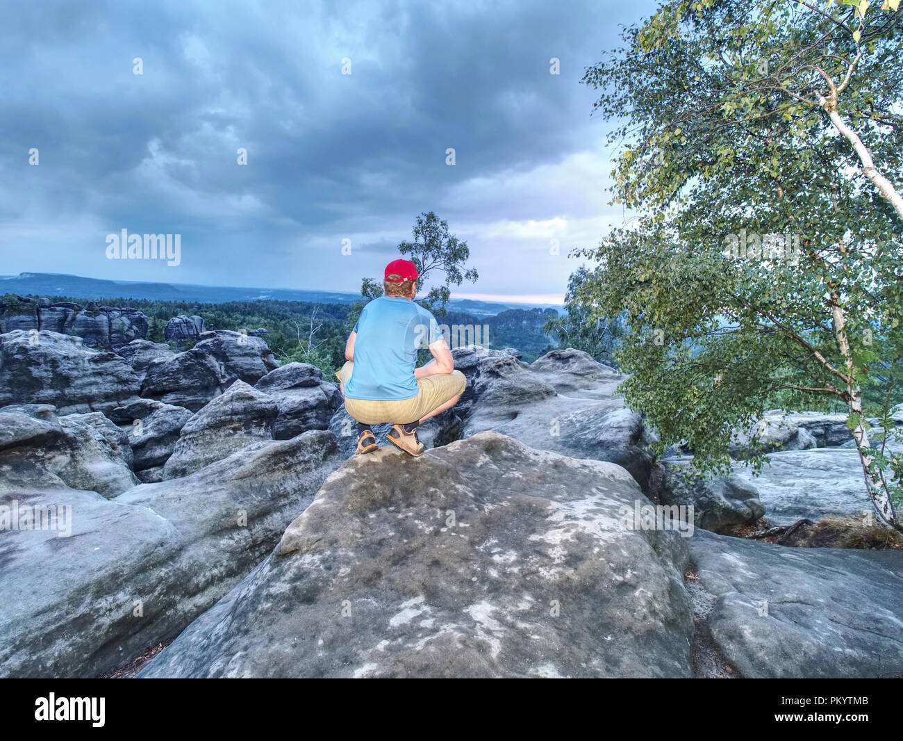 Runner on the peak. Hiker in running trousers and shinning blue sweaty t-shirt. Man in his target. - Stock Image