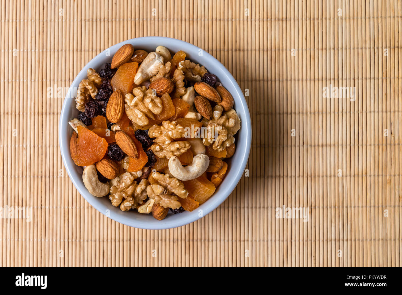 Mixed nuts and fruits in a white bowl - Stock Image