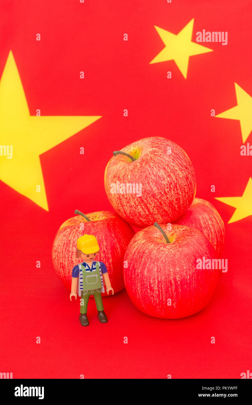 U.S red apple exports with Chinese flag and small toy farmer - metaphor US apple industry, Chinese trade tariffs on imports of U.S apples. - Stock Image