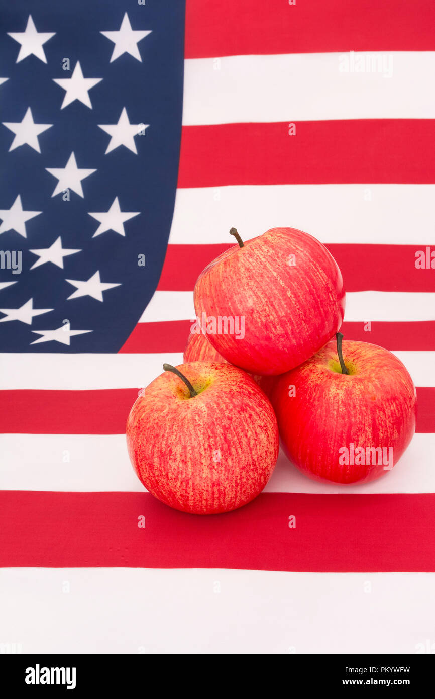 Red apples with U.S. American flag / Stars and Stripes - metaphor US apple industry, Apple Day,  and Chinese trade tariffs on imports of U.S. apples. Stock Photo