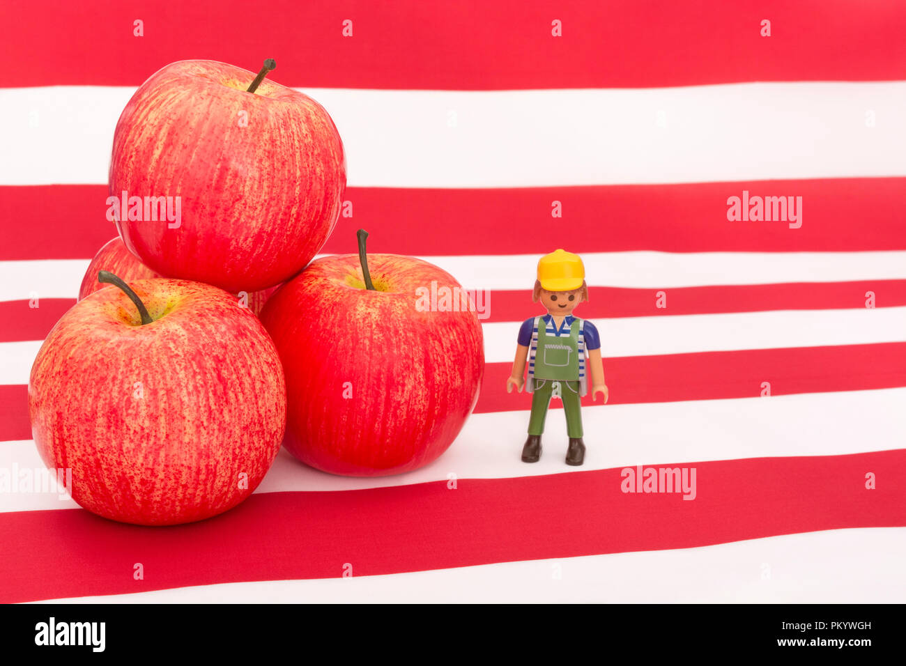 Red apples with U.S. American flag / Stars and Stripes - metaphor US apple industry, Chinese trade tariffs on imports of U.S. apples. Small toy farmer. - Stock Image