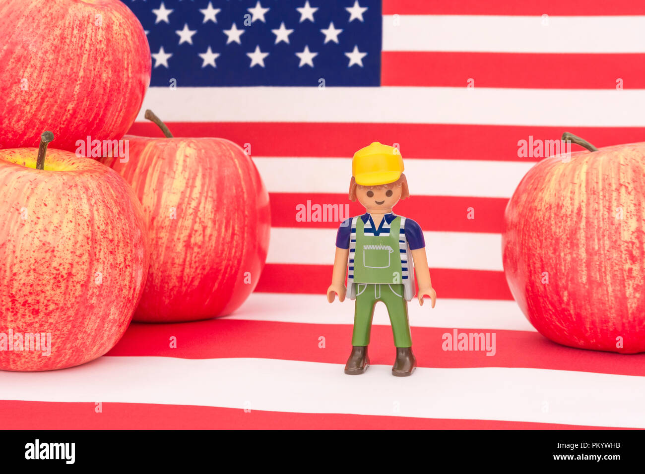Red apples + US American flag / Stars and Stripes - metaphor US apple industry, Chinese trade tariffs on imports of American apples. Small toy farmer Stock Photo