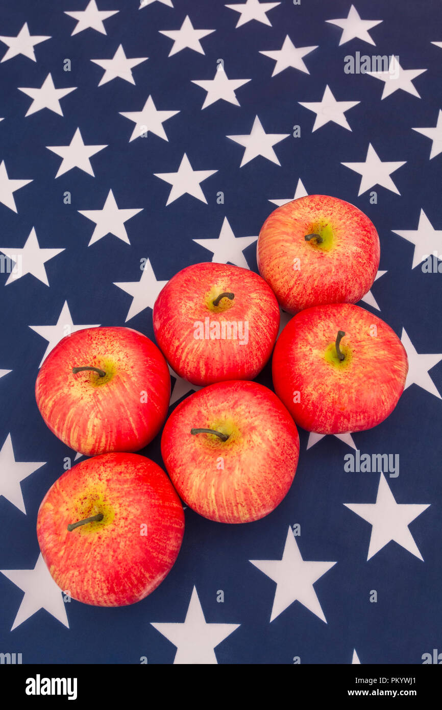 Red apples with US American flag / Stars and Stripes - metaphor US apple industry, Apple Day, and Chinese trade tariffs on imports of US apples. Stock Photo