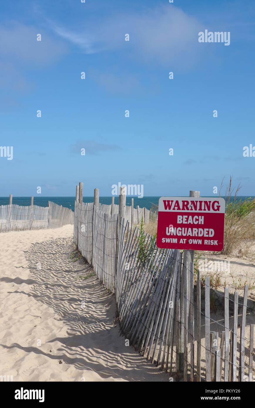 Unguarded beach signage after the summer swim season. - Stock Image