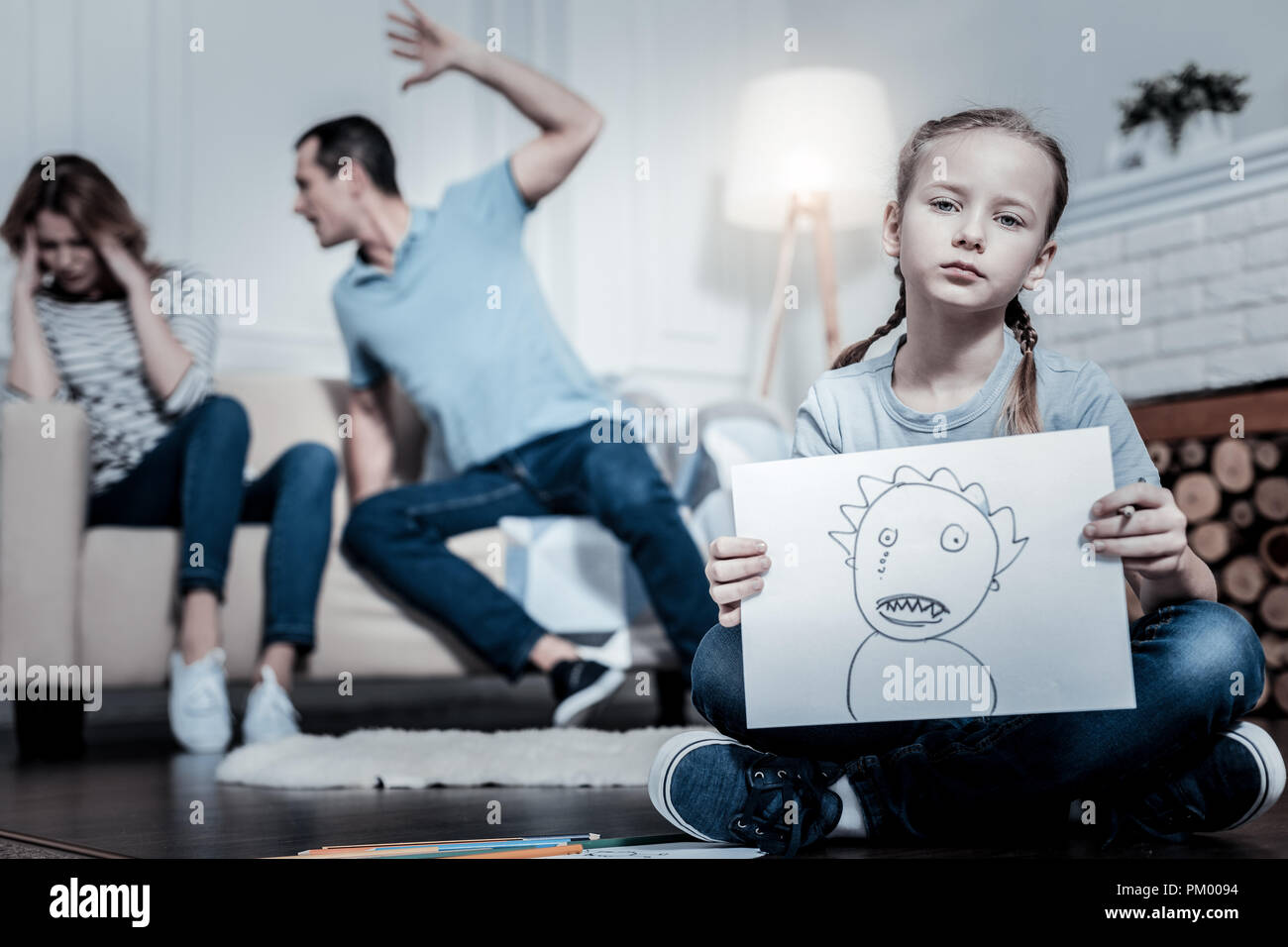 Indifferent kid showing a picture - Stock Image