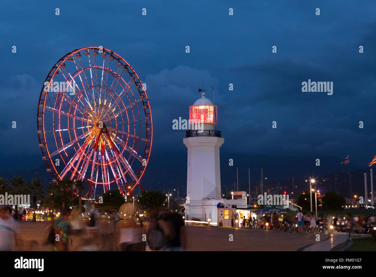 Night view on the illuminated ferris wheel and lighthouse in Batumi, Georgia - Stock Image
