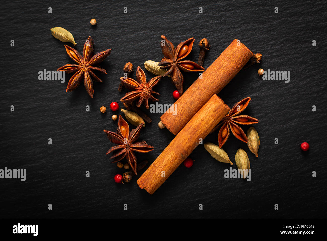 Food background close up organic various spices on black slate board Stock Photo
