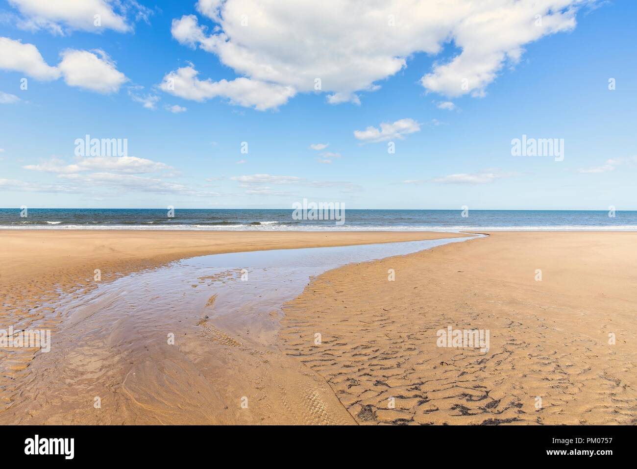 A wide stretch of water narrows as it runs to the sea across the beach.  A blue sky with clouds is above. Stock Photo