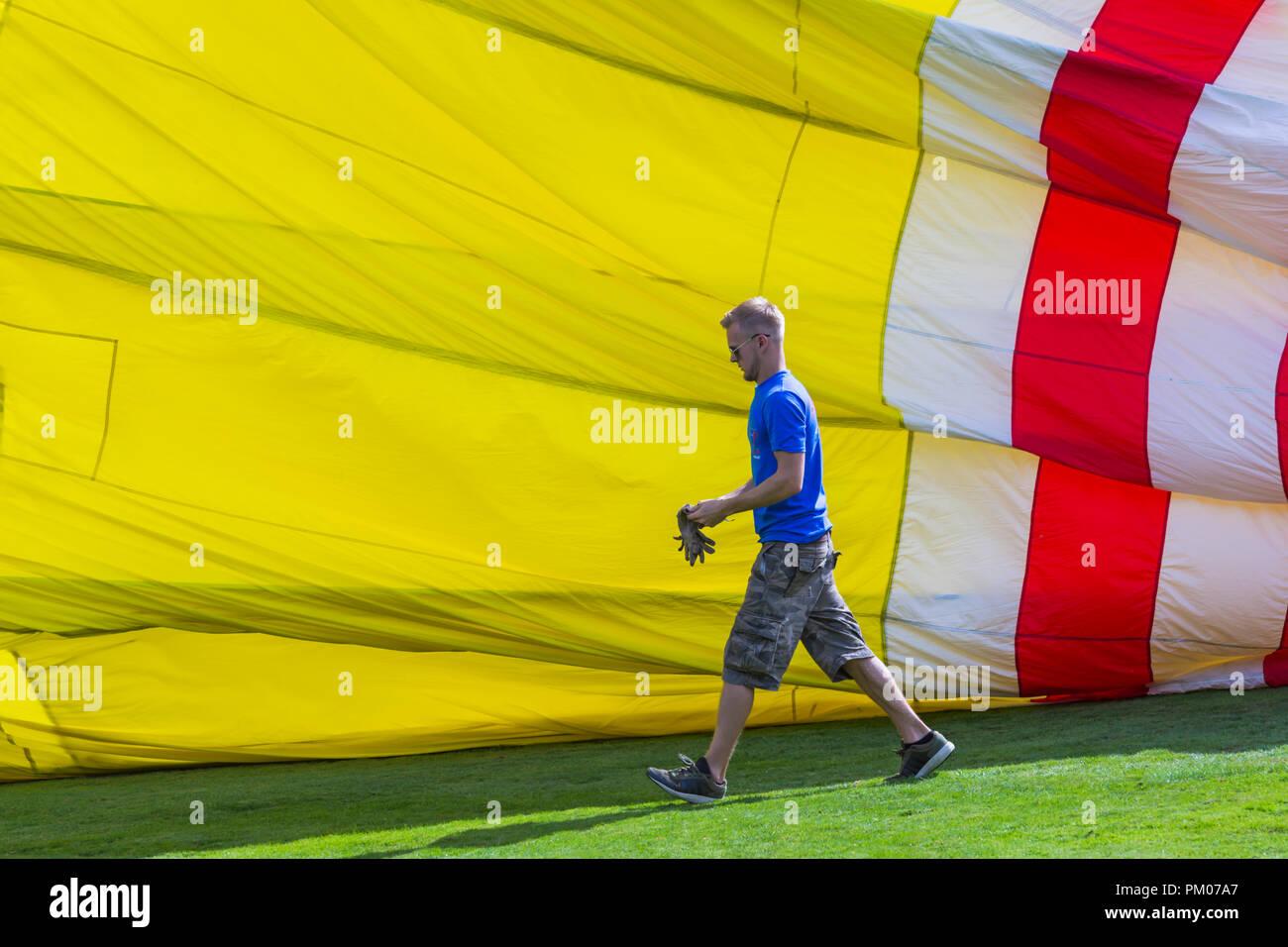 man putting on gloves walking past colourful balloon, preparing hot air balloon at Longleat Sky Safari, Wiltshire, UK in September - Stock Image