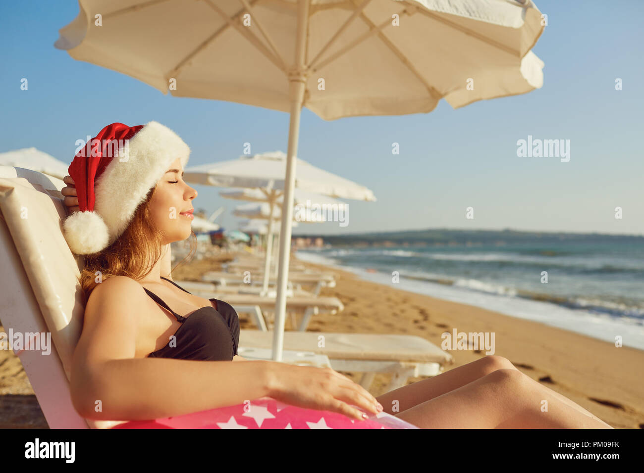 Girl in santa hat on the beach by the sea on Christmas Day.  - Stock Image