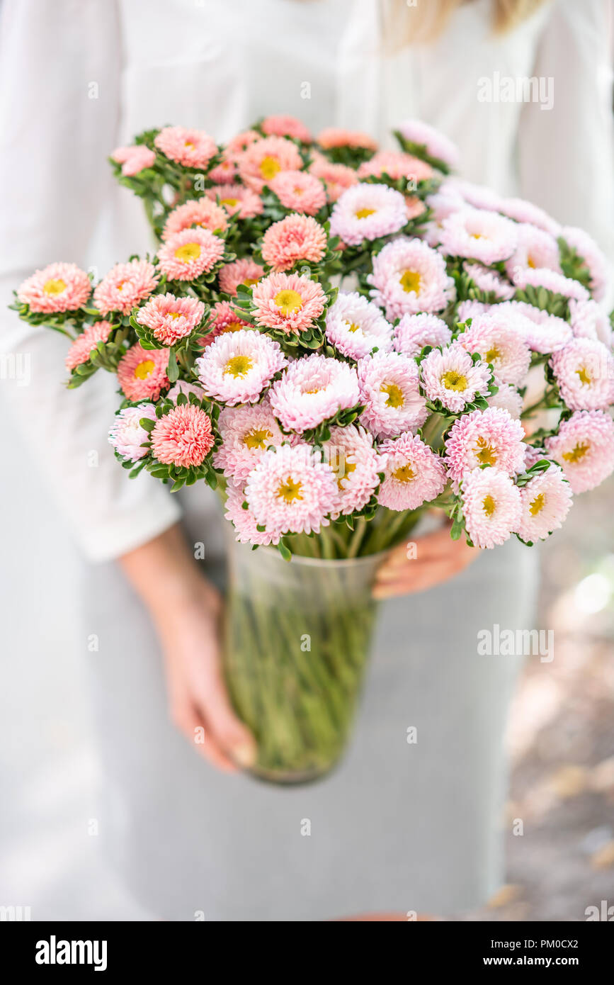 Vase With Beautiful Aster Flower Bouquet In Womens Hand Vase With
