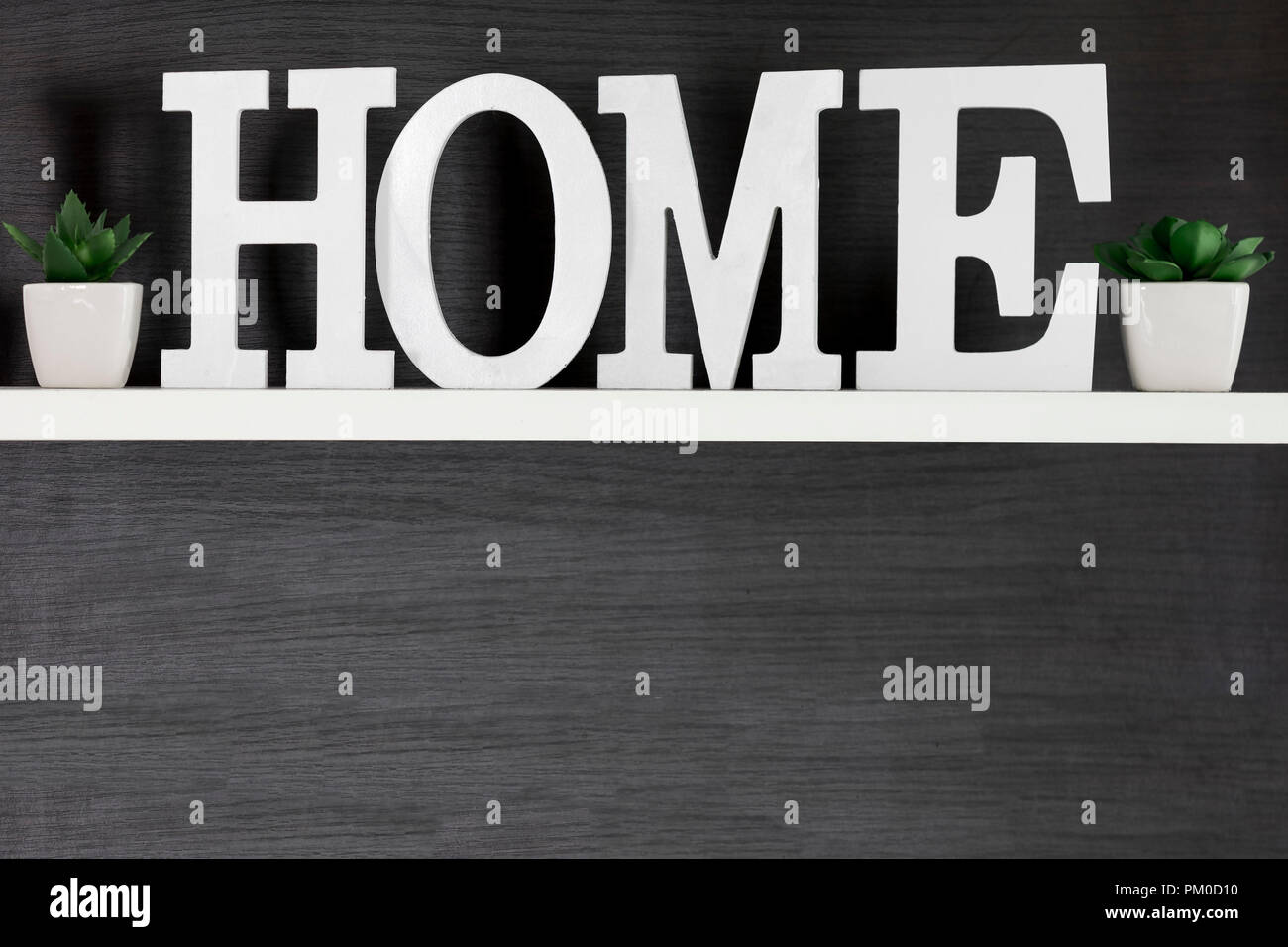 Home letters decor on white shelf with dark wood background, copy space - Stock Image