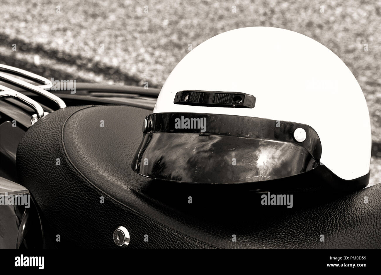 Closeup of motorcycle headlights, helmet in black and white. - Stock Image