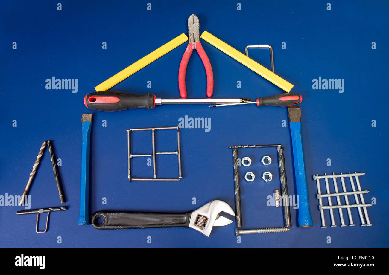 Construction concept house built out of building supplies.  Nails, pliers, screwdrivers and more. - Stock Image