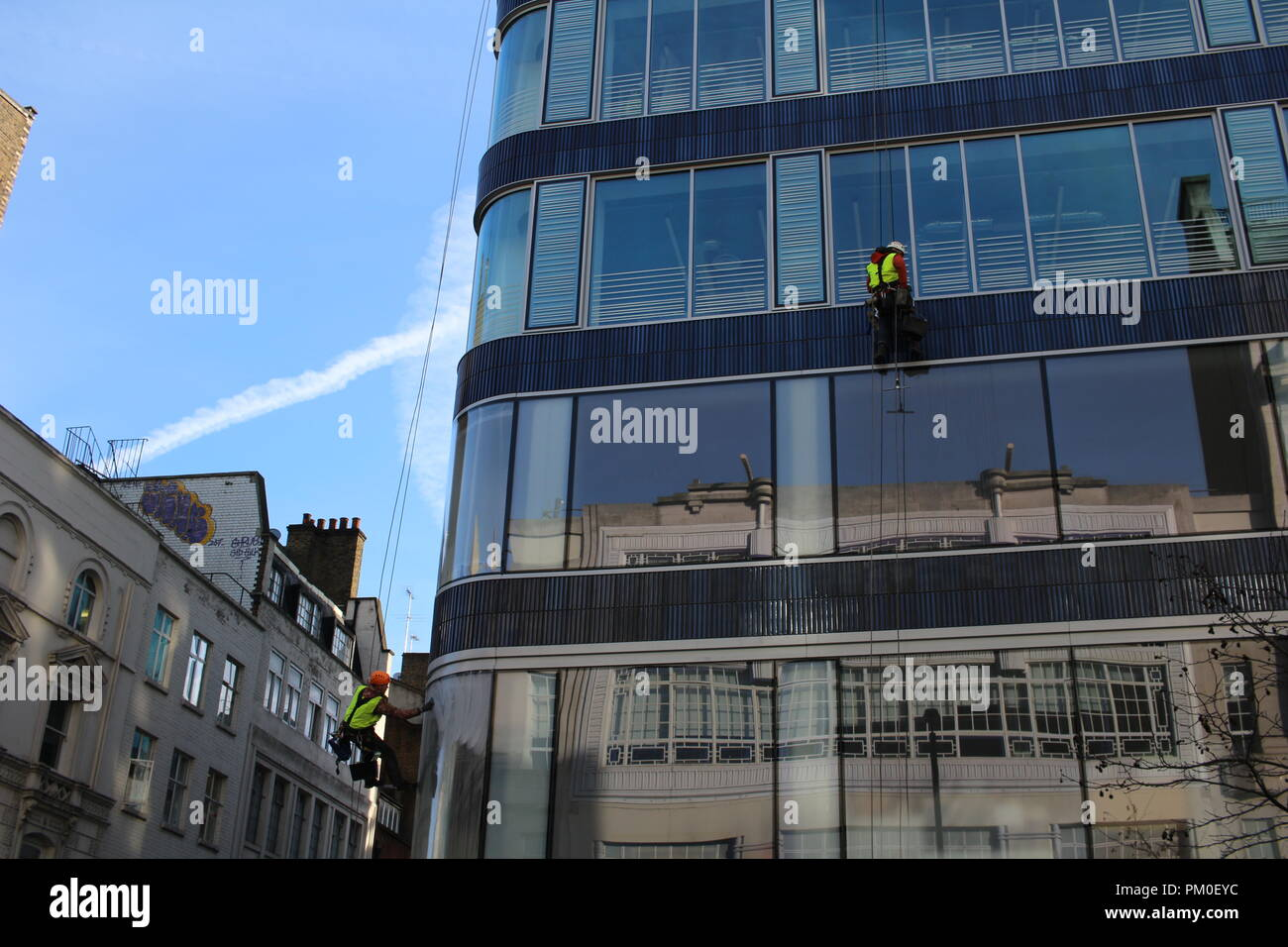 LONDON, UK - February 16, 2018: Oxford  street; a group of workers cleaning washing windows on high rise building. - Stock Image