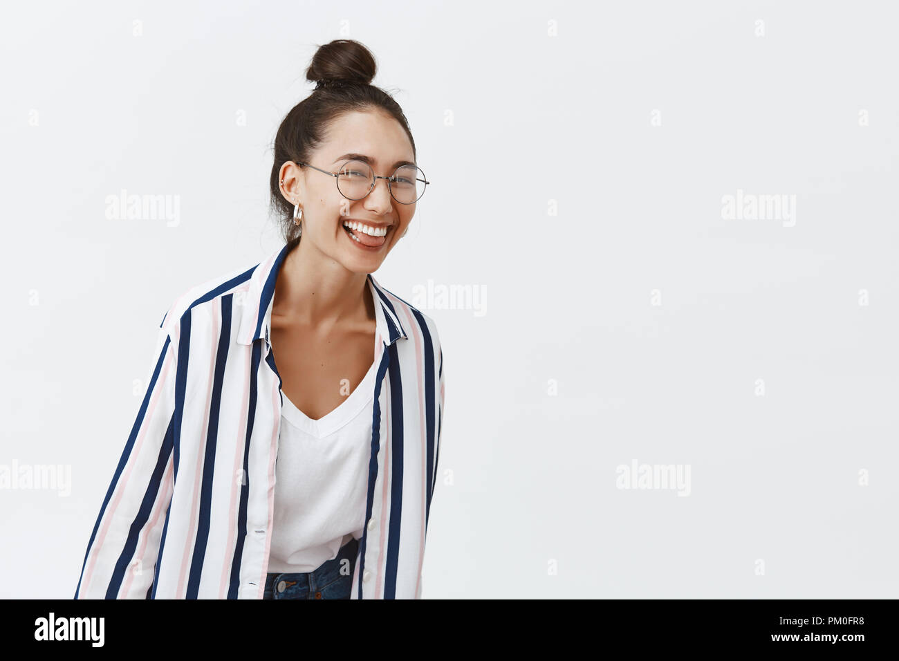 Girl just wanna have fun. Studio shot of charming playful woman leading active and happy lifestyle, bending towards camera while laughing over funny joke, standing in trendy outfit and glasses Stock Photo