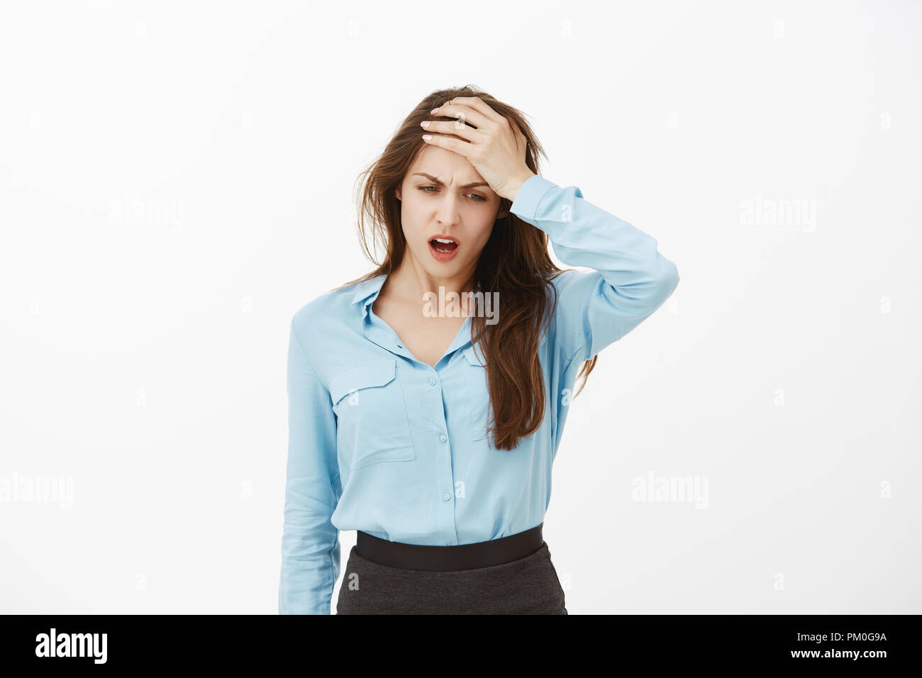 Waist-up shot of displeased gloomy european woman in blue blouse, holding palm on forehead and frowning, looking down, feeling like mess, having headache or suffering from hangover over grey wall Stock Photo