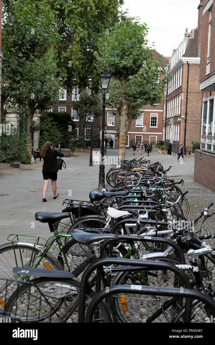 Woman walking past parked bicycles in bike stand at Grays Inn, Central London WC1 UK  KATHY DEWITT - Stock Image