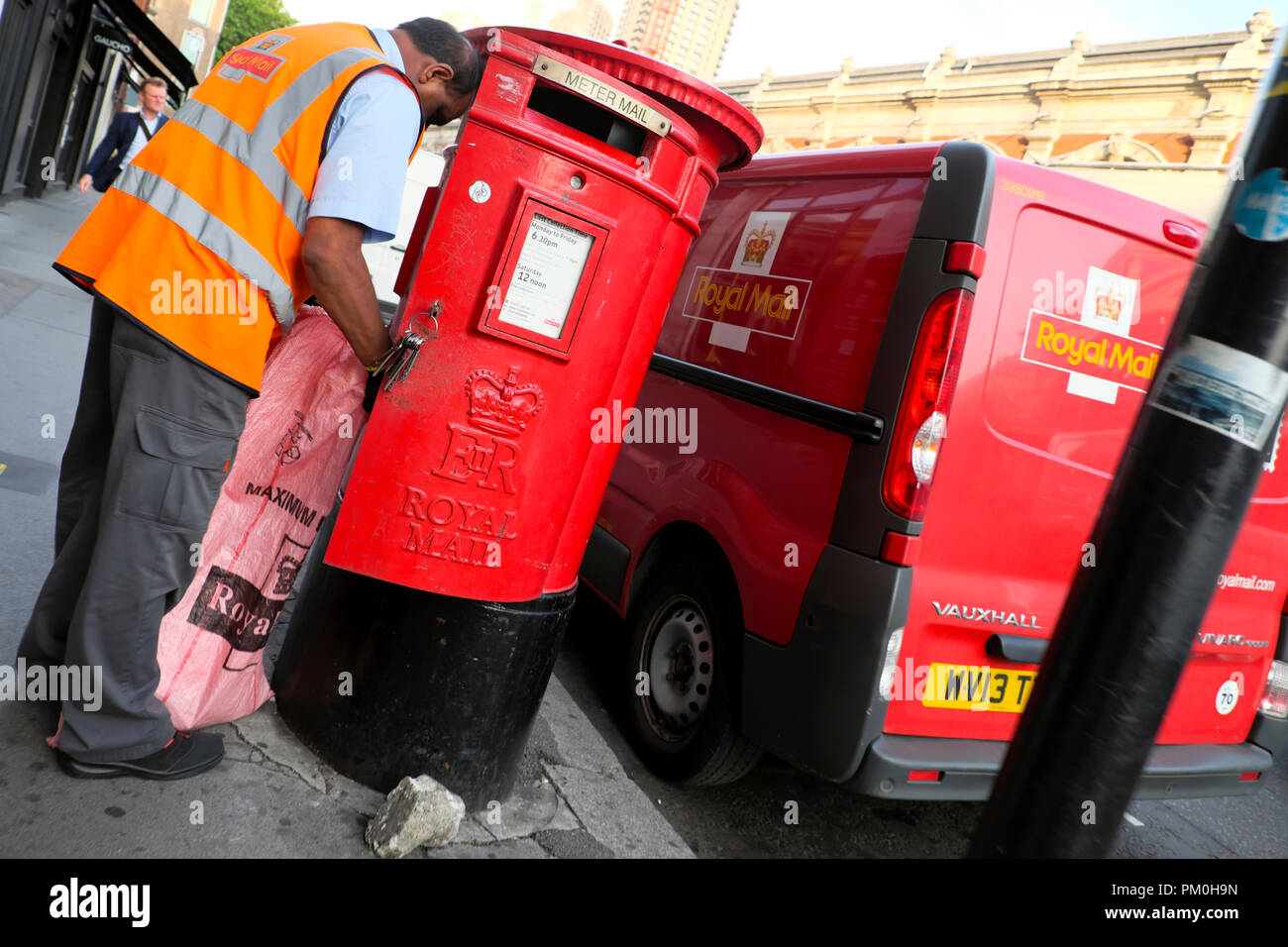 Royal Mail postal worker transferring mail into a sack bag from a red post box to his postal van in Charterhouse St Smithfield London UK  KATHY DEWITT - Stock Image