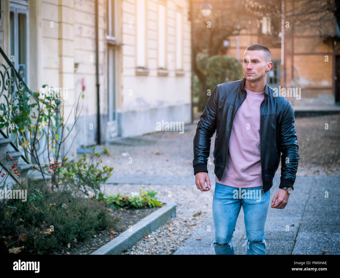 17e1f08a One handsome young man in urban setting in European city, standing, wearing  black leather jacket and jeans