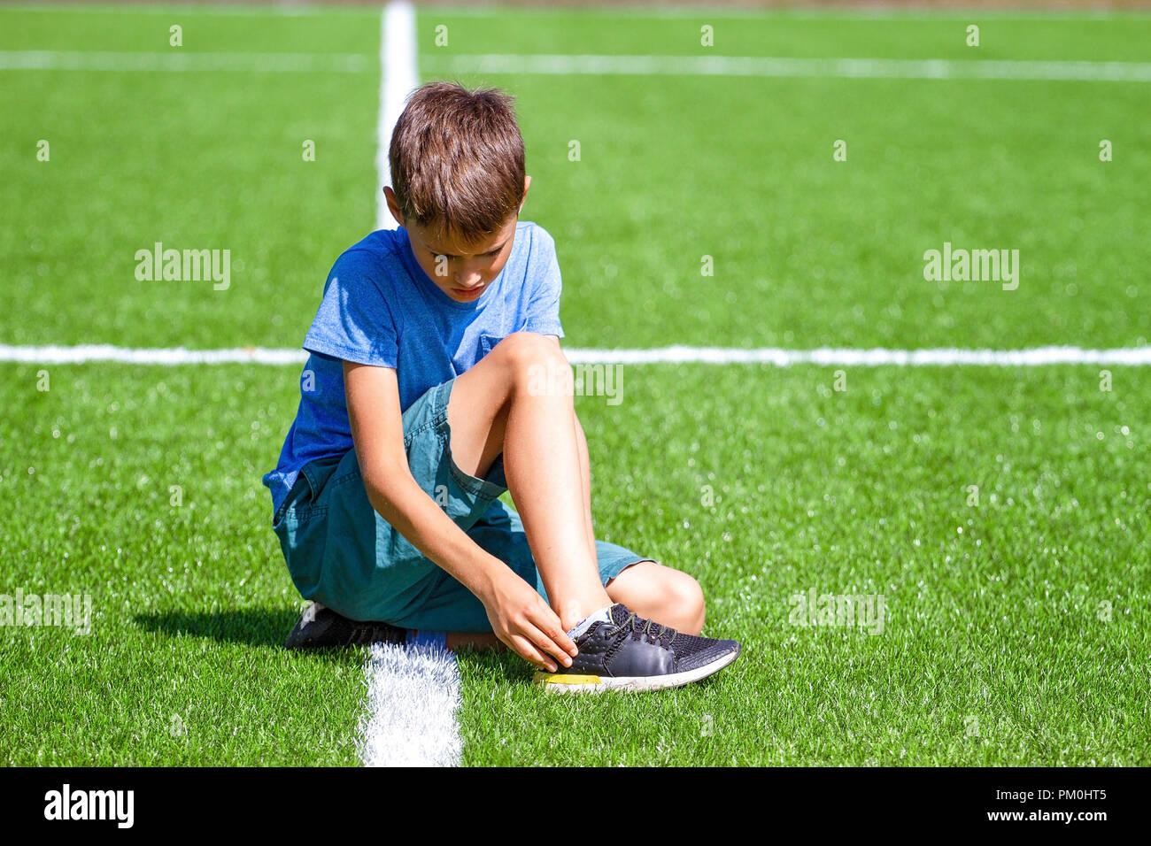 Boy injured his leg. Child sitting on the grass at soccer football stadium - Stock Image