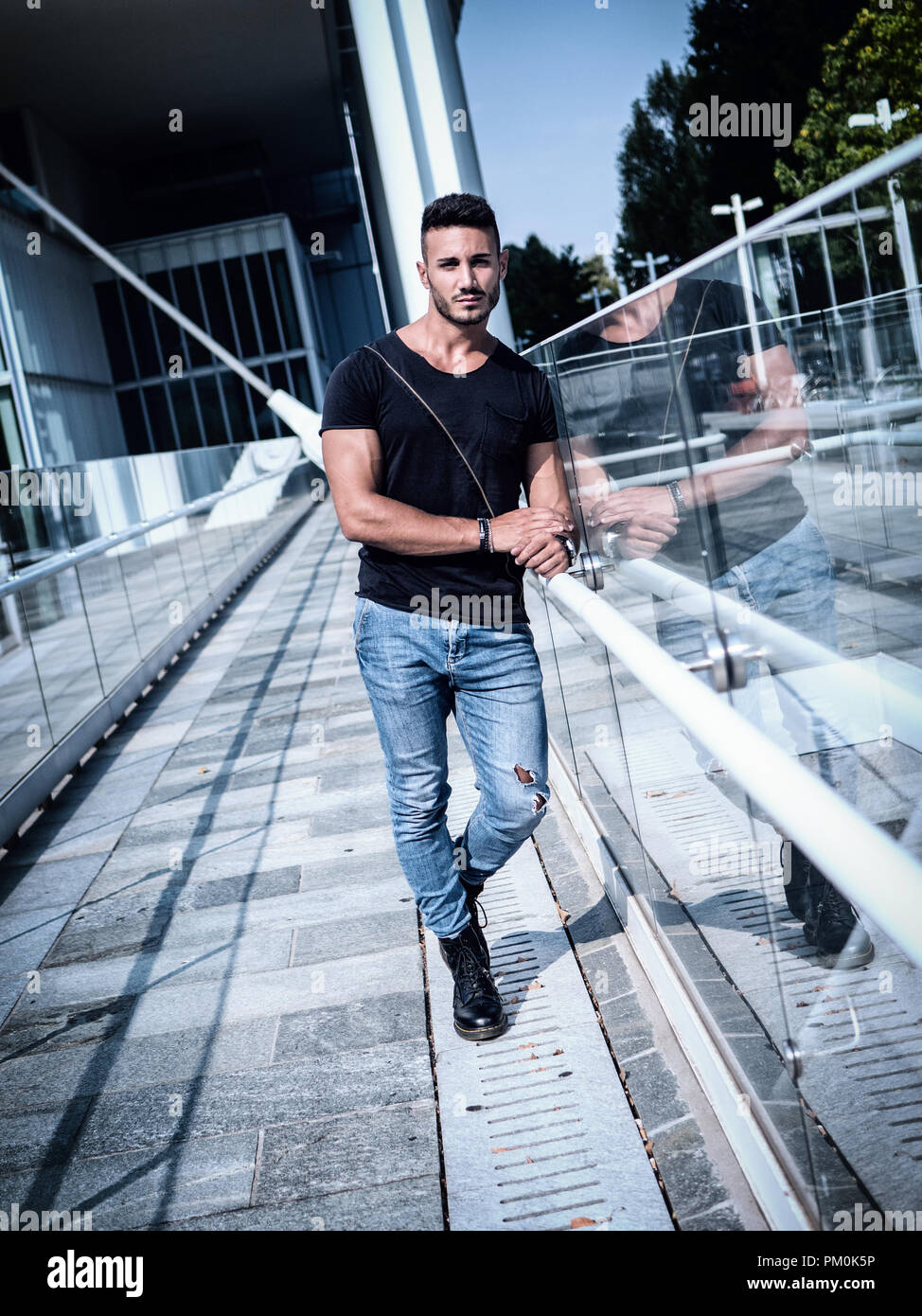 367e1bcb One handsome young man in urban setting in European city, wearing jeans and  black t-shirt