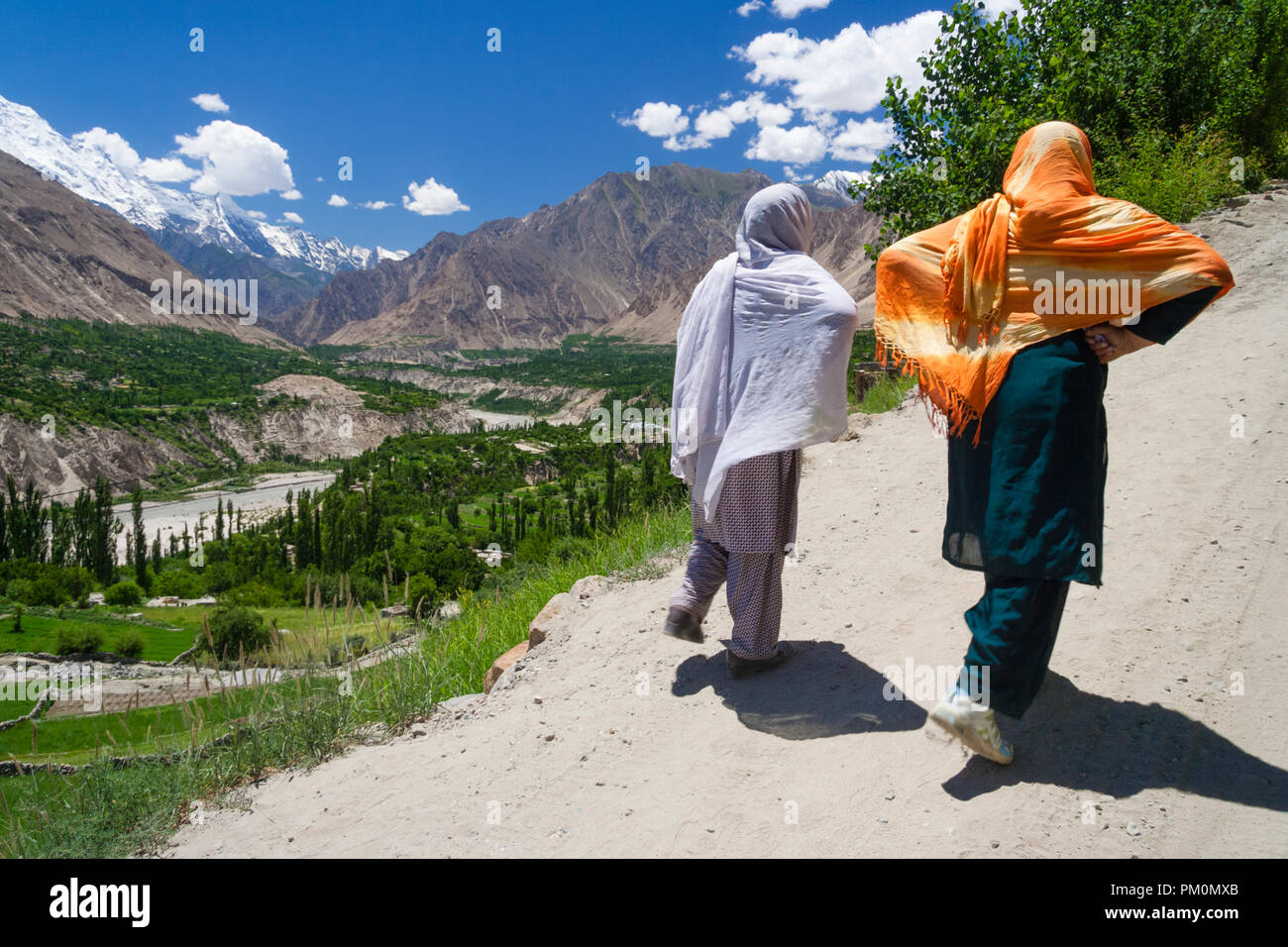 Karimabad, Hunza Valley, Gilgit-Baltistan, Pakistan : Two young women walk towards the mountain town of Karimabad (formerly Baltit) the capital of the - Stock Image